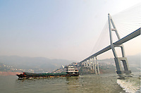 "Barges and container ships pass under a new bridge on the ""ribbon lake"" of the Yangtze River in China. The construction of the Three Gorges Dam and rise in water level of around 100 meters, creating a narrow lake 450 km in length and has resulted in the relocation of around 1.5 million people. The Dam has opened up central China, with ocean going vessels able to travel as far as Chongqing, and is transforming the economy.."