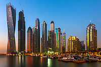 Colorful sunrise on the modern, lit-up marina skyscrapers, with boats in the foreground in Dubai, United Arab Emirates, Asia