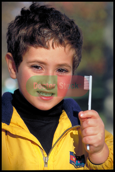 serious young boy holding toothbrush