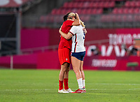 KASHIMA, JAPAN - AUGUST 2: Christine Sinclair #12 of Canada and Lindsey Horan #9 of the USWNT embrace after the game between Canada and USWNT at Kashima Soccer Stadium on August 2, 2021 in Kashima, Japan.