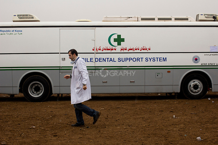 DOMIZ, IRAQ: A dentist walks past a 'mobile dental support system' in the Domiz refugee camp in the Kurdish region of northern Iraq...The semi-autonomous region of Iraqi Kurdistan has accepted around 60,000 refugees from war-torn Syria. Around 20,000 refugees live in the Domiz camp which sits 60 km from the Iraq-Syria border...Photo by Younes Mohammad/Metrography