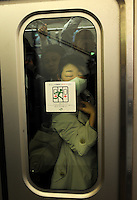 A female passenger squashed against the glass on a train during rush-hour in Shinjuku Station, Tokyo, Japan. With up to 4 million passengers passing through it every day, Shinjuku station, Tokyo, Japan, is the busiest train station in the world. The station was used by an average of 3.64 million people per day.  That's 1.3 billion a year.  Or a fifth of humanity. Shinjuku has 36 platforms, and connects 12 different subway and railway lines.  Morning rush hour is pandemonium with all trains 200% full. <br /> <br /> Photo by Richard jones / sinopix