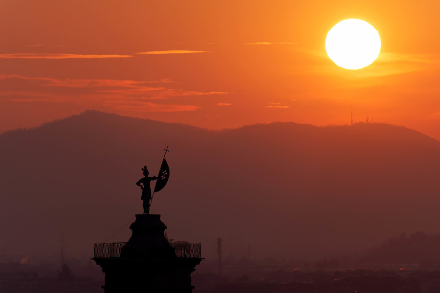 Statue on top of bell tower at Church of Sant'Alessandro della Croce silhouetted against sunrise, Bergamo, Italy