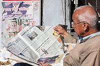 India, Dehradun.  Man Reading his Morning Newspaper in Hindi.