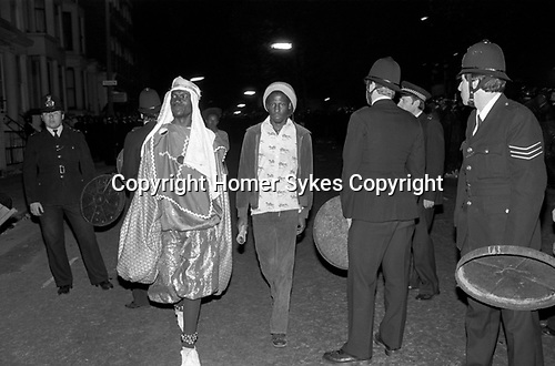 Notting Hill Carnival 1980s. Police use dustbin lids as shield as trouble, begins. Two revellers walk through group of police. 1981