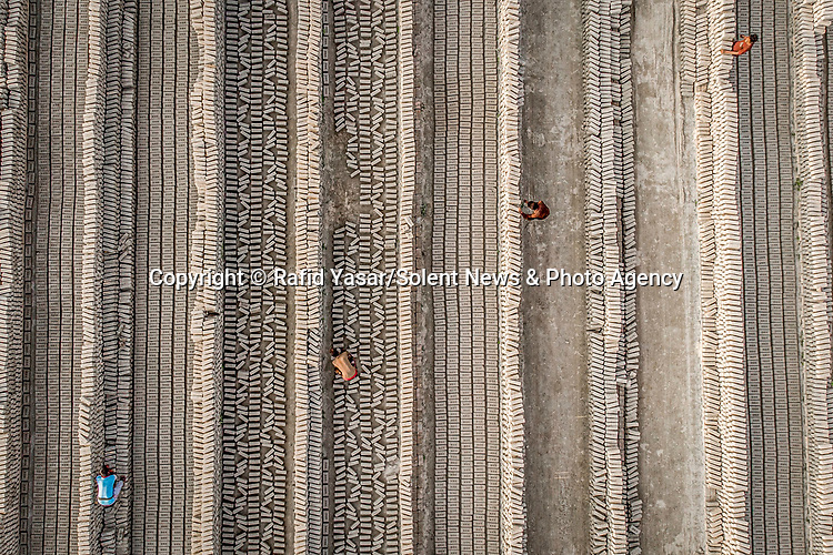 Workers toss each other bricks at an enormous factory.  The huge factory is one of the biggest in Bangladesh and has more than 10 million of the building blocks in its storage.<br /> <br /> Aerial photographs of the site in Mokamtala, Bogra, show the factory's workers covering unfinished bricks with blue plastic sheets.  University student Rafid Yasar, who captured the shots using a drone, said the labourers work from 7am until 5.30pm six days a week, earning 200 Bangladeshi Taka per day - equivalent to £1.68.  SEE OUR COPY FOR DETAILS.<br /> <br /> Please byline: Rafid Yasar/Solent News<br /> <br /> © Rafid Yasar/Solent News & Photo Agency<br /> UK +44 (0) 2380 458800
