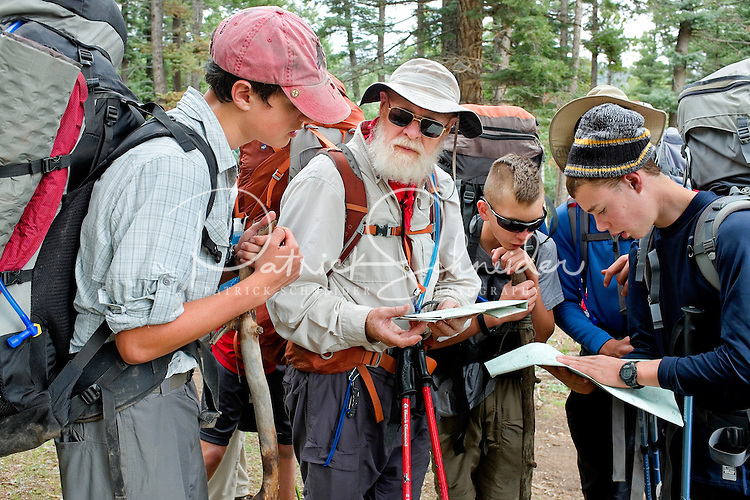 Photo story of Philmont Scout Ranch in Cimarron, New Mexico, taken during a Boy Scout Troop backpack trip in the summer of 2013. Photo is part of a comprehensive picture package which shows in-depth photography of a BSA Ventures crew on a trek.  In this photo BSA Venture Crew Scouts and adult advisors work together to review the map as they confirm their trail direction choice in the backcountry at Philmont Scout Ranch.   <br /> <br /> The  Photo by travel photograph: PatrickschneiderPhoto.com