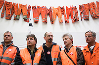 Switzerland. Canton Ticino. Bellinzona. Railway workers on strike listen to the mass on Easter sunday at Officine FFS. Catholic religious service. Stabilimento Industriale SBB CFF FFS Cargo. . Building's occupation. Orange clothes of the blue collar workers are hanged on the wall. © 2008 Didier Ruef