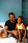 Kwame Mwakio and his daughter at home.  Kwame overseas scholarship programs in Likoni, Kenya for the Hatua Likoni Foundation