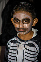 "Oaxaca, Mexico, North America.  Day of the Dead Celebrations.  This boy's facial make-up is representative of an ""Angelito"", a Little Angel, symbolizing children who die before having their First Communion.  He is participating in a ""comparsa"", a procession of children in costume, to celebrate the Day of the Dead, when Oaxacans honor their dead ancestors."