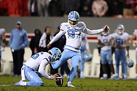 RALEIGH, NC - NOVEMBER 30: Noah Ruggles #97 of the University of North Carolina attempts a field goal with the hold by Cooper Graham #96 during a game between North Carolina and North Carolina State at Carter-Finley Stadium on November 30, 2019 in Raleigh, North Carolina.