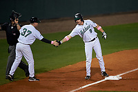 Stetson Hatters coach Mark Levitt (37) high fives Will Mackenzie (9) during a game against the Siena Saints on February 23, 2016 at Melching Field at Conrad Park in DeLand, Florida.  Umpire Ray Parrish calls time on the left.  Stetson defeated Siena 5-3.  (Mike Janes/Four Seam Images)