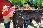 Mike Murphy, right, transfers the mochila to Marvin Davis during the Pony Express Re-ride in Fredricksburg, Ca., on Thursday, June 14, 2012. About 600 riders retrace the historic route to deliver the mochila full of mail from Sacramento to St. Joseph, Missouri. In it's 152nd year, the event spans 10 days and 1,966 miles. .Photo by Cathleen Allison