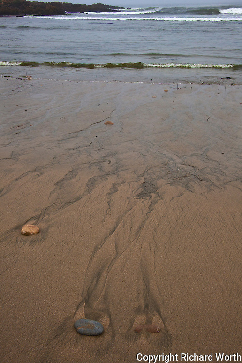 Rocks embedded in wet, brown sand help paint 'sand trails' by guiding, nudging and obstructing the receding waters of low tide along California's Pescadero State Beach south of San Francisco.