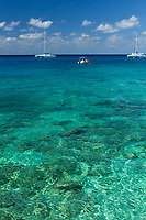Beautiful, turquoise, and transparent Caribbean Sea, with white catamaran boats under a blue sky with white clouds, Cozumel Island, Mexico