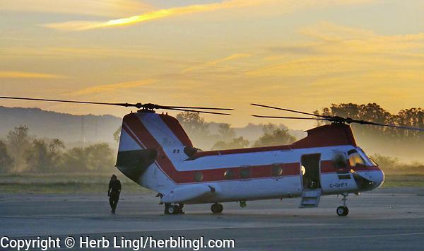 A Boeing Vertol CH-46 Sea Knight twin rotor helicopter based in British Columbia, Canada prepares for takeoff at dawn at the Petaluma Municipal Airport, Petaluma, Sonoma County, California.