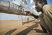 A man examines a leaking oil pipe line at a pumping station built next to his village on land that was once used for agriculture.