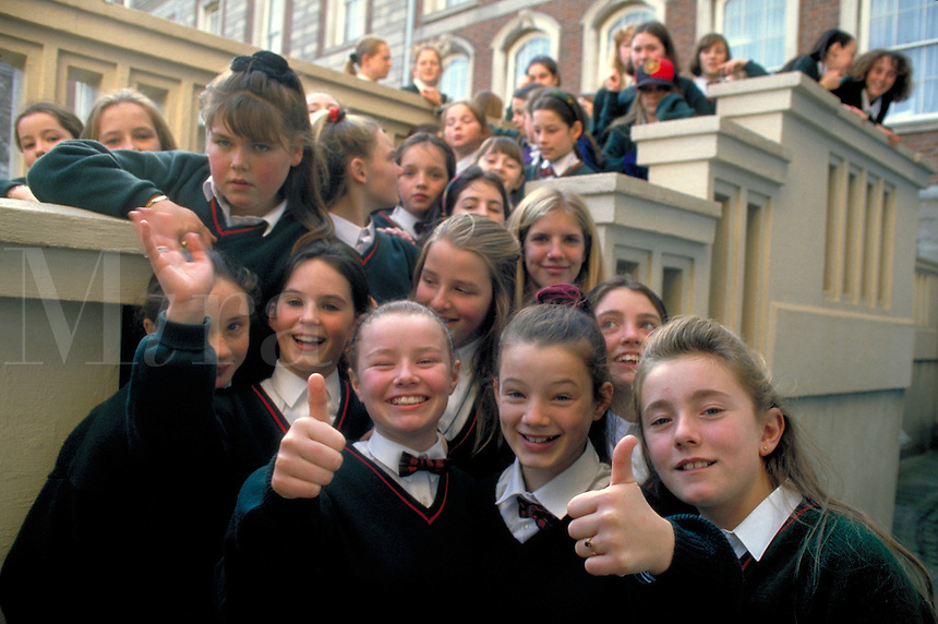 A group of smiling schoolgirls clad in school uniform pose for the camera during a field trip to the Royal Palace in Dublin. Dublin, Ireland.