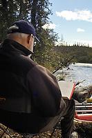 Edward Bennett reads a book along the Gulkana River in Alaska on a sunny summer day.