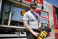 Firefighter Hayden Johnson inspects a chain saw, Friday, April 30, 2021 at the Lowell Fire Department in Lowell. Lowell will hold a special election May 10 for voters to extend a current 1 cent sales tax which funds about 70 percent of the city's operating budget. A bulk of the money goes to the fire department, police department and roads. Check out nwaonline.com/210501Daily/ for today's photo gallery. <br /> (NWA Democrat-Gazette/Charlie Kaijo)