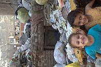 2011 Mokattam Garbage City (alla periferia del Cairo) il quartiere copto dove si vive in mezzo alla spazzatura raccolta: due bambine sorridono in mezzo ai sacchi dell'immondizia. Sullo sfondo case nuove in costruzione.