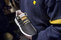 """Adidas-BVG-Turnschuh.<br /> Verkauf des Adidas-BVG-Turnschuh """"Sneaker EQT Support 93"""", im Berliner Turnschuhgeschaeft """"Overkill"""" am Dienstag den 16. Januar 2018.<br /> Der Turnschuh, der auch bis zum 31.12.2018 als BVG-Jahreskarte gueltig ist, wird in einer limitierten Auflage von 500 Stueck verkauft. Jugendlichen und professionelle eBay-Haendler sind bereits seit zwei Tagen Vorort um den Turnschuh fuer 180,- Euro zu kaufen. Die eBay-Haendler wollen den Turnschuh fuer mind. 2.000,-€ verkaufen.<br /> Im Bild: Ein BVG-Mitarbeiter mit dem Turnschuh.<br /> 16.1.2018, Berlin<br /> Copyright: Christian-Ditsch.de<br /> [Inhaltsveraendernde Manipulation des Fotos nur nach ausdruecklicher Genehmigung des Fotografen. Vereinbarungen ueber Abtretung von Persoenlichkeitsrechten/Model Release der abgebildeten Person/Personen liegen nicht vor. NO MODEL RELEASE! Nur fuer Redaktionelle Zwecke. Don't publish without copyright Christian-Ditsch.de, Veroeffentlichung nur mit Fotografennennung, sowie gegen Honorar, MwSt. und Beleg. Konto: I N G - D i B a, IBAN DE58500105175400192269, BIC INGDDEFFXXX, Kontakt: post@christian-ditsch.de<br /> Bei der Bearbeitung der Dateiinformationen darf die Urheberkennzeichnung in den EXIF- und  IPTC-Daten nicht entfernt werden, diese sind in digitalen Medien nach §95c UrhG rechtlich geschuetzt. Der Urhebervermerk wird gemaess §13 UrhG verlangt.]"""