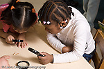 Preschool 4-5 year olds nature study two girls looking at meal worms on table holding magnifying glasses horizontal