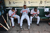 OAKLAND, CA - JUNE 6:  Robert Andino #12 (left),Melvin Mora #6 and Felix Pie #18 of the Baltimore Orioles get ready in the dugout before the game against the Oakland Athletics at the Oakland-Alameda County Coliseum on June 6, 2009 in Oakland, California. Photo by Brad Mangin