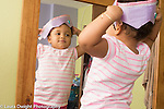 18 month old toddler girl at home looking at self in mirror recognizing self wearing dressup crown