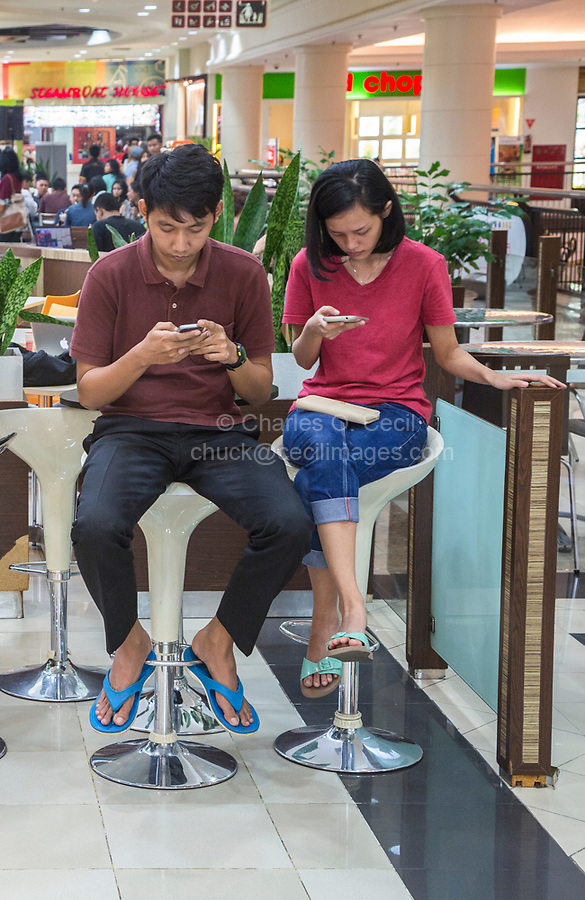 Yogyakarta, Java, Indonesia.  Ambarrukmo Shopping Mall.  Young Javanese Couple Checking Cell Phones in the Food Court.