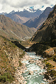 Inca Trail to Machu Picchu, Peru. Andean rocky mountain stream running through a deep valley with snow capped mountains.