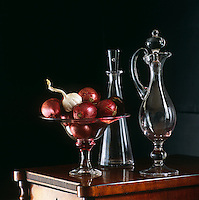 A pair of contemporary glass decanters and a glass bowl of red onions with a bulb of garlic on a Victorian mahogany sideboard