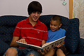 MR / Little Falls, NY. Boy left (16) reads to his cousin (5, Korean-American & Caucasian, learning disabled). MR: Smi4, Sti4. ID: AJ-gsf. © Ellen B. Senisi