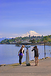 Two girls look towrad Mt. Rainier from a telescope at Les Davis Park on Tacoma's Commencement Bay.  Commencement Bay with the Cascade Mountains in background, as seen from the south shore and Foss Waterway.  Commencement Bay's history of industry and shipping has led it to designation as a Superfund Cleanup Site and one of the most polluted waterways in the nation.  Commencement Bay Nearshore/Tideflats (CB/NT) Superfund Site.