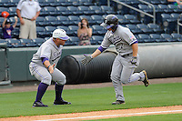 Third baseman Chris Ohmstede (7) of the Furman Paladins is greeted by the third base coach after hitting a home run in a game against the Elon Phoenix in the first round of the Southern Conference Tournament game on Wednesday, May 22, 2013, at Fluor Field at the West End in Greenville, South Carolina. Furman won, 10-1. (Tom Priddy/Four Seam Images).
