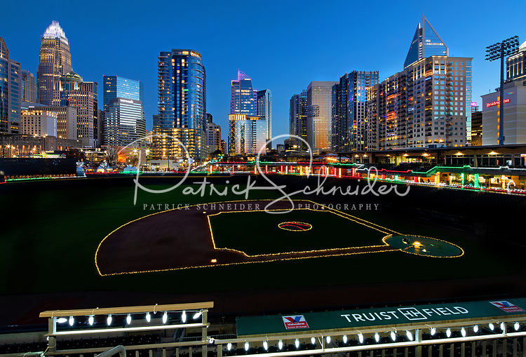 Photography of the The Charlotte Knights Light the Knights and Charlotte Christmas Village at Truist Field in Uptown Charlotte, North Carolina. The Christmas experience allows visitors to walk thru Christmas Tree Lane and see thousands of lights on display. Visitors to the Christmas display can stroll around the circumference of Truist Field taking in the lights against the backdrop of the Uptown Charlotte Skyline as well as visiting the Charlotte Christmas Village. <br /> <br /> Charlotte Photographer - PatrickSchneiderPhoto.com