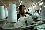 An Indian woman working with a coputerized Siruba flat lock machine(made in Japan) at Popy's garment stitching factory in Tirupur, Tamilnadu. After lifting of quota system in textile export on 1st january 2005. Tirupur has become the biggest foreign currency earning town of India.