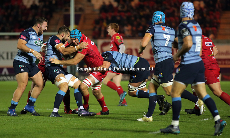 Tadhg Beirne of the Scarlets (C) is tackled by two Cardiff Vlues players during the Guinness PRO14 match between Scarlets and Cardiff Blues at Parc Y Scarlets Stadium, Llanelli, Wales, UK. Saturday 28 October 2017