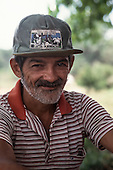 """Xapuri, Acre State, Brazil. Portrait of a bearded rubber tapper wearing a hat with """"Rio Branco, Capital of Rubber"""" on the badge."""