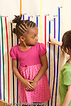 Education preschool 3-4 year olds two girls looking at height measured in colored tape on the wall vertical