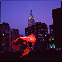 Dancer in red on roof with Empire State Building in background<br />