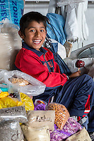 Peru, Cusco, San Pedro Market.  Young Boy Eating a Candied Apple.