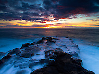 Waves wash over a lava rock shelf during a vibrant sunset off of Keahole Point, Big Island.