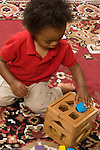 16 month old toddler baby boy kneeling on floor playing with shape sorter toy vertical