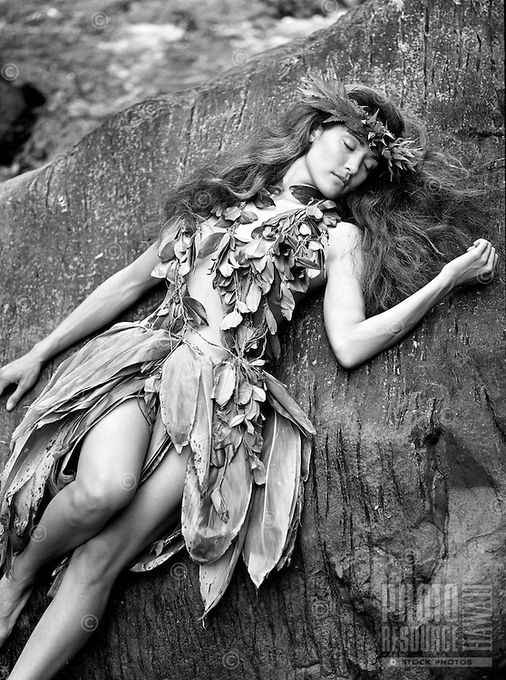 Young Hawaiian girl resting on a rock near a stream, wearing maile lei, ti leaf skirt and lei po'o.