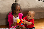 6 year old girl showing baby brother, age 12 months, how a new toy works, jack-in-the-box