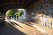 Pedestrians and cyclist pass under a bridge, Vienna.