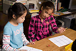Education Elementary Grade 3 math activity two girls playing game  that students made, rolling dice