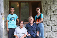 Durovic Jovo, winemaker, seated with his wife and son and daughter standing in front of the winery. Durovic Jovo Winery, Dupilo village, wine region south of Podgorica. Vukovici Durovic Jovo Winery near Dupilo. Montenegro, Balkan, Europe.