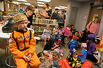 After completing a Halloween craft project Hayden Brundage, 6, left, and other children watch TV at the Carson City Library Monday, Oct. 27, 2014. As part of the library's Halloween festivities, dozens of children decorated pumpkins or gourds and took part in a costume contest.